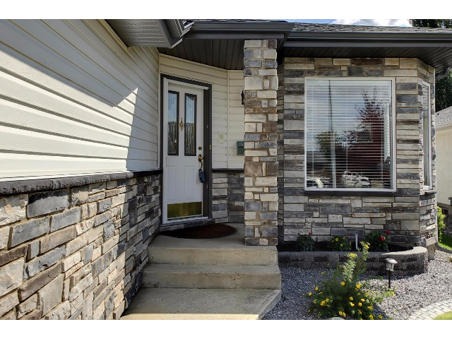 The entrance to this home is now so improved! The stone facing adds personality and takes maintenance away. Note the sprinkler system in the flower bed by the front window.