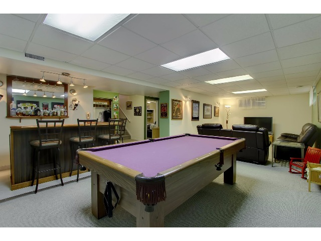 The view from one end of the basement family/recreation room is highlighted by the new carpeting, the games area, the bar and the consistent lighting.